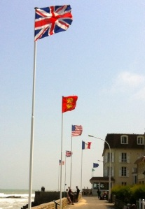 Flags of Britain, Canada, United States, and France along the beach in Arromanches, France