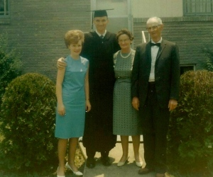 My first wife Bettye, me in my graduation duds, Mother, and Daddy. We were in front of the house where we rented a basement apartment.