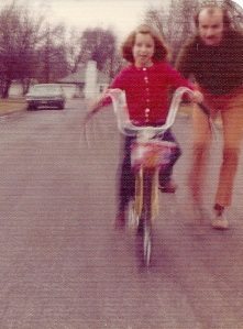 My daughter Joy with me helping balance her bike, mid 1970s.
